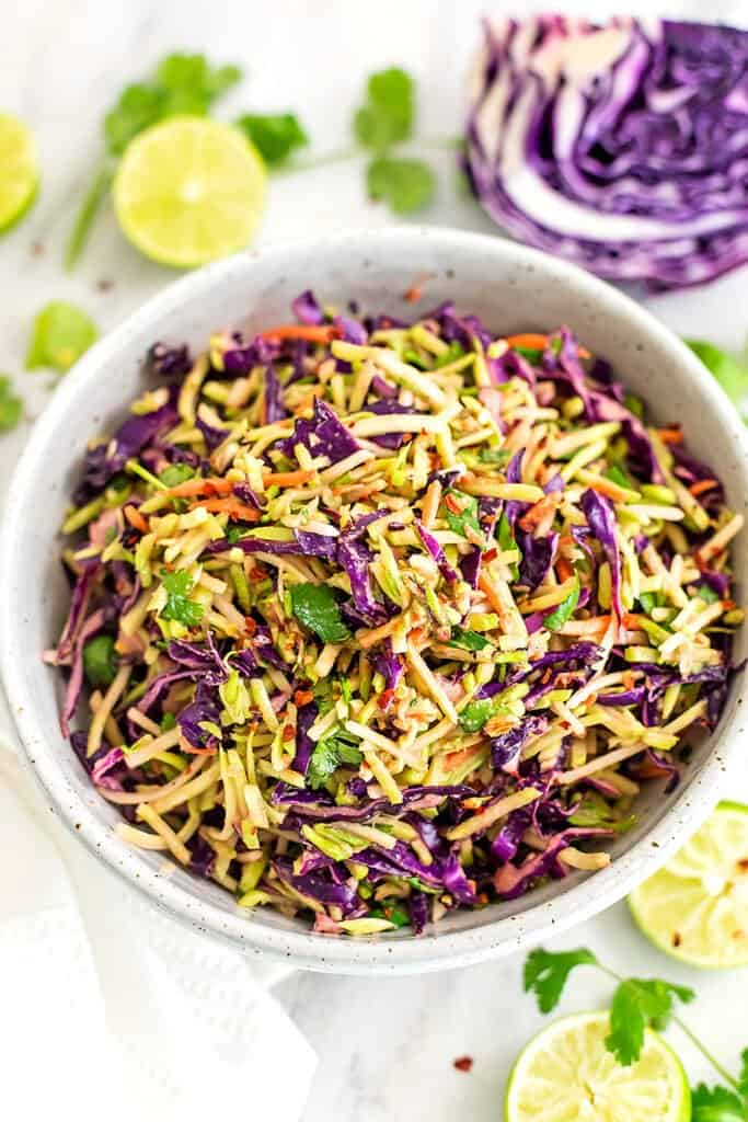 Large bowl of sesame ginger broccoli slaw with cabbage in background.