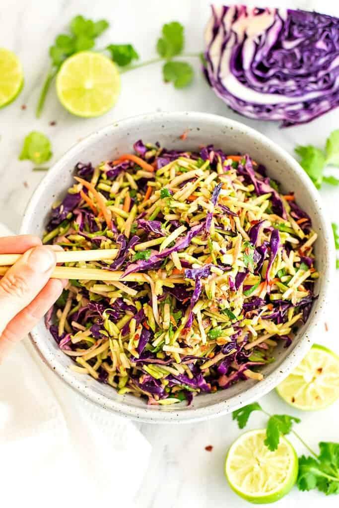Chop sticks in a bowl of asian broccoli slaw.