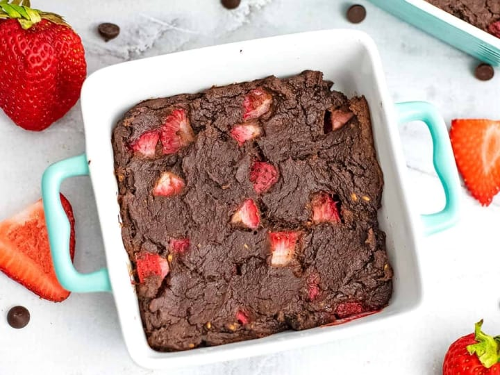 Square ramekin filled with single serve brownie with strawberries