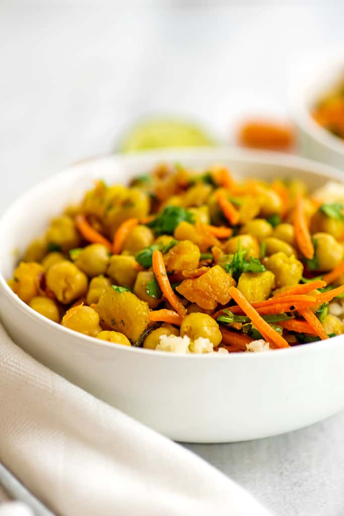 Bowl of apricot chickpea curry with white napkin.