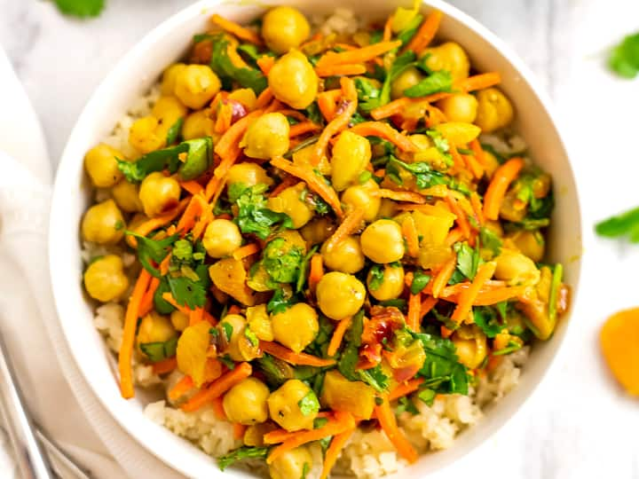 Apricot chickpea curry in a white bowl over cauliflower rice.