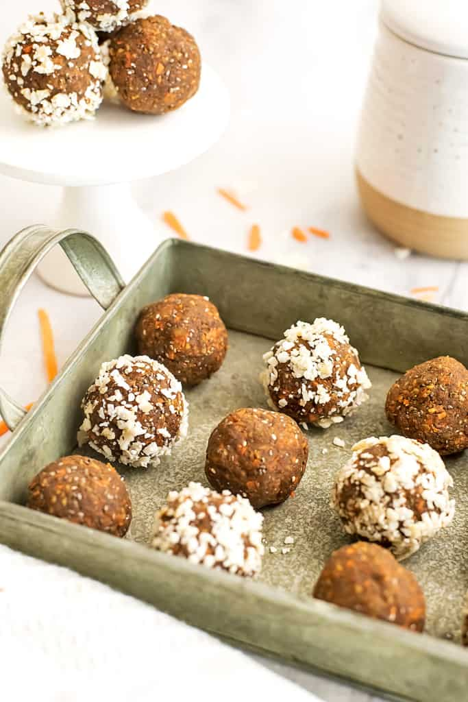 Carrot cake protein balls in a green tray with more in background.