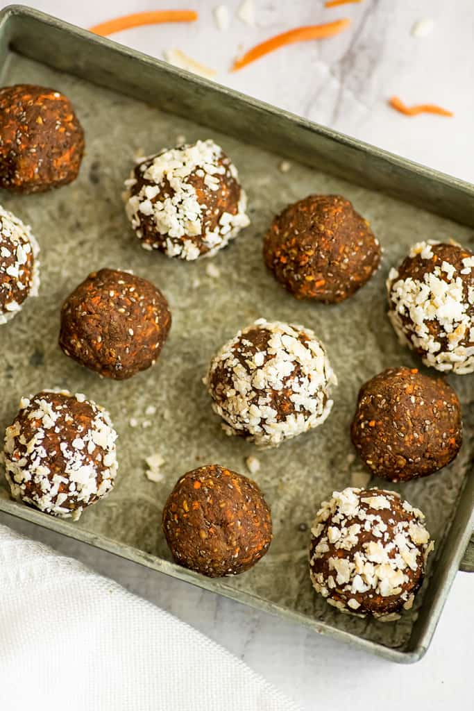 Carrot cake energy bites lined up on a tray.