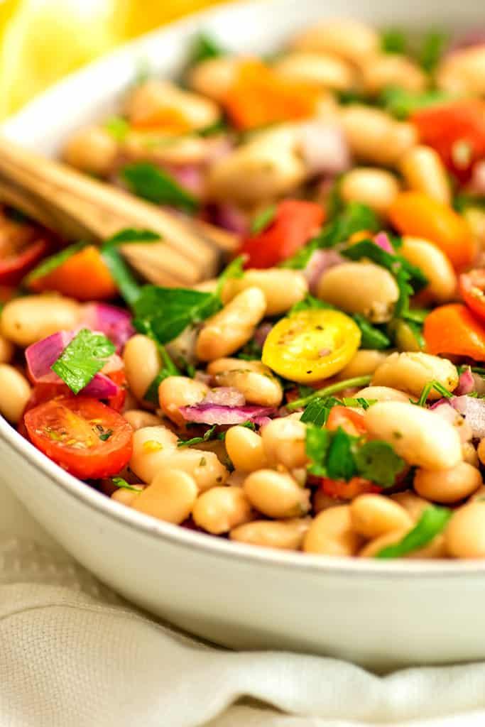 Mediterranean white bean salad in a white bowl.