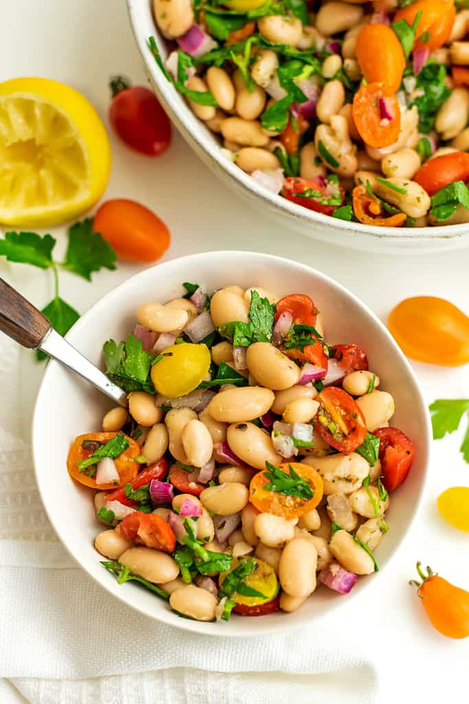 Small white bowl filled with greek white bean salad and a spoon.