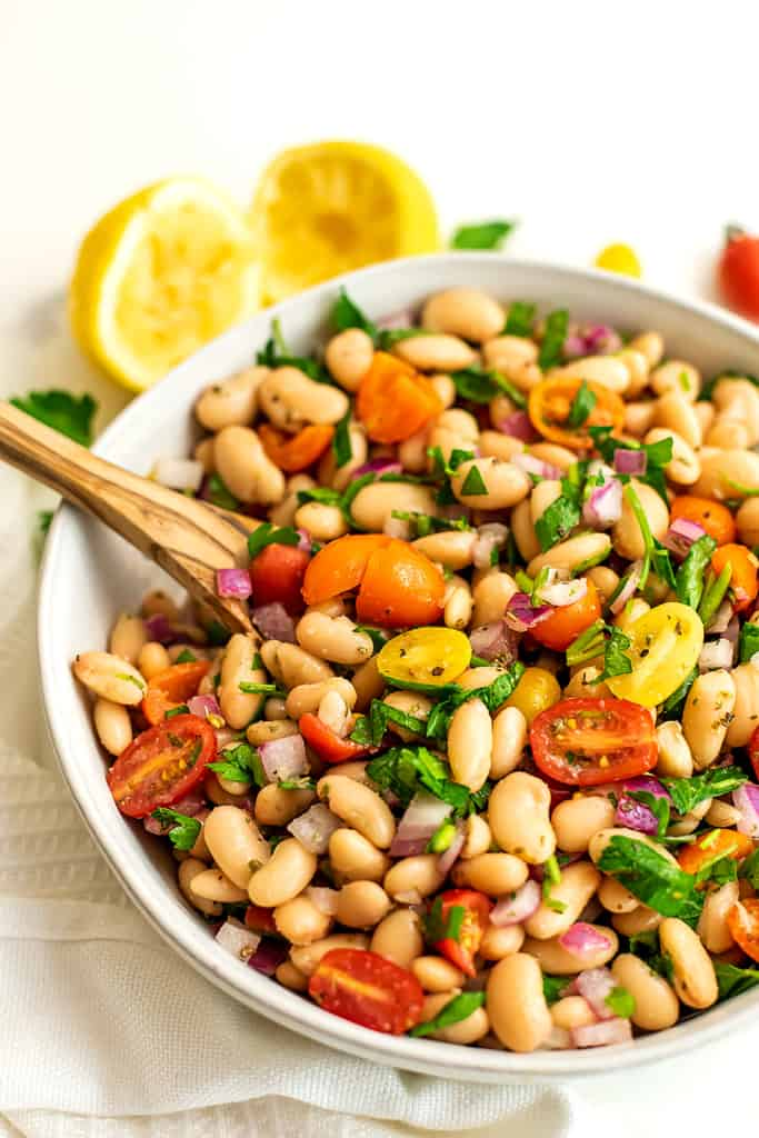 Serving dish filled with greek white bean salad and wooden spoon.