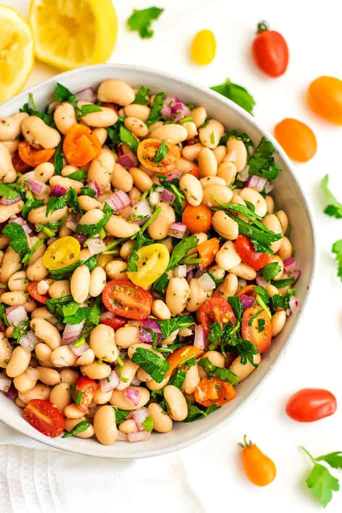 Large bowl filled with Mediterranean white bean salad.