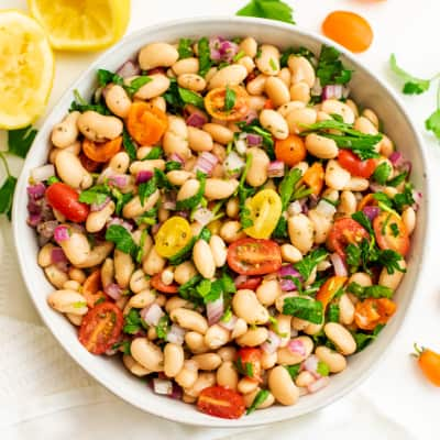 Greek white bean salad in a bowl with lemons in background.