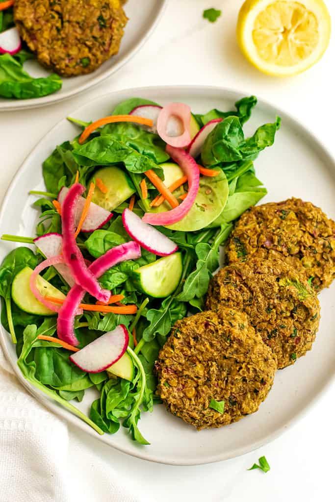 Plate of salad and 3 lentil falafels.