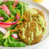 Plate of salad and 3 lentil falafel with green tahini drizzle.