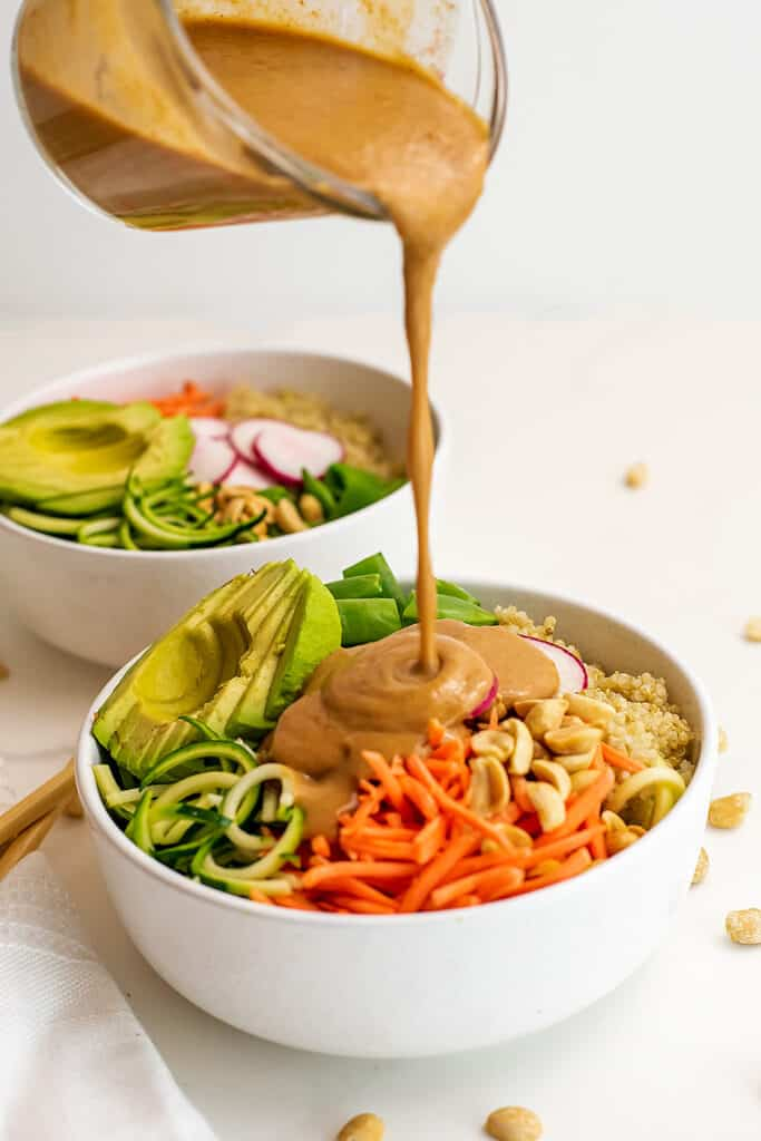 Peanut dressing being poured over asian zoodle bowl.