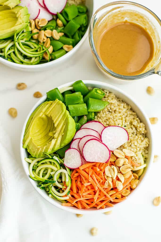 Asian zoodle buddha bowl in a white bowl with peanut dressing.