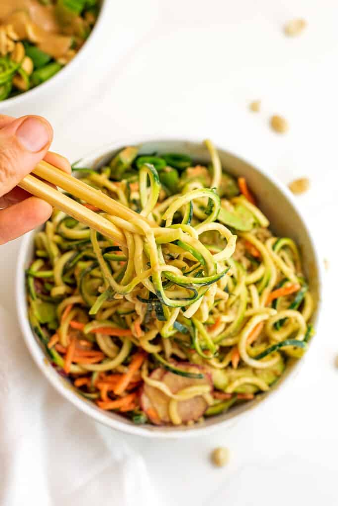 Chopsticks grabbing zucchini noodles from a zoodle bowl.