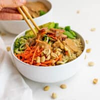 Chopsticks in a bowl filled with zucchini noodles and peanut dressing.