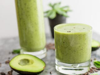 Mint avocado protein shake in a glass with avocado next to the glass.