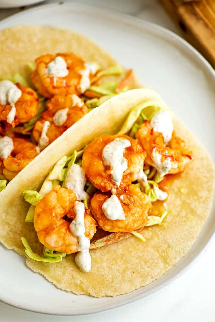 Buffalo grilled shrimp taco with slaw and ranch dressing.