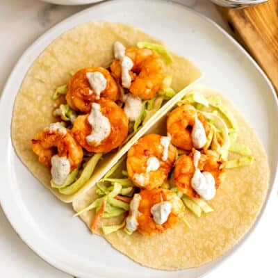 Two buffalo grilled shrimp tacos with ranch drizzle on a plate.