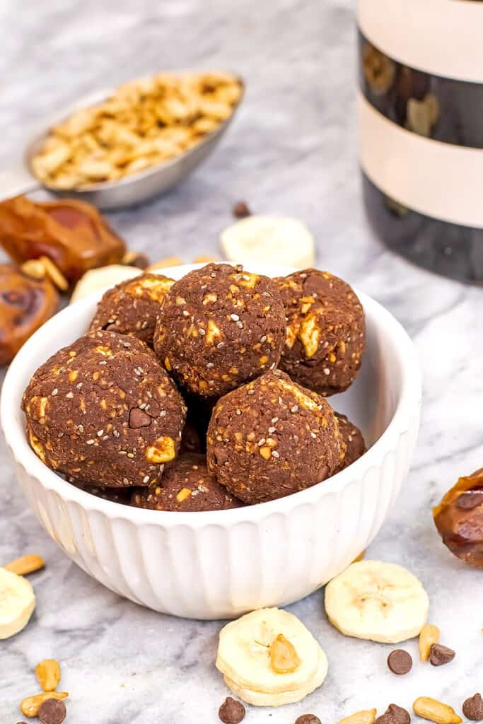 bowl filled with chocolate banana protein balls with dried bananas around bowl.