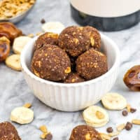 Bowl filled with chocolate banana protein balls with chocolate chips and bananas around bowl.