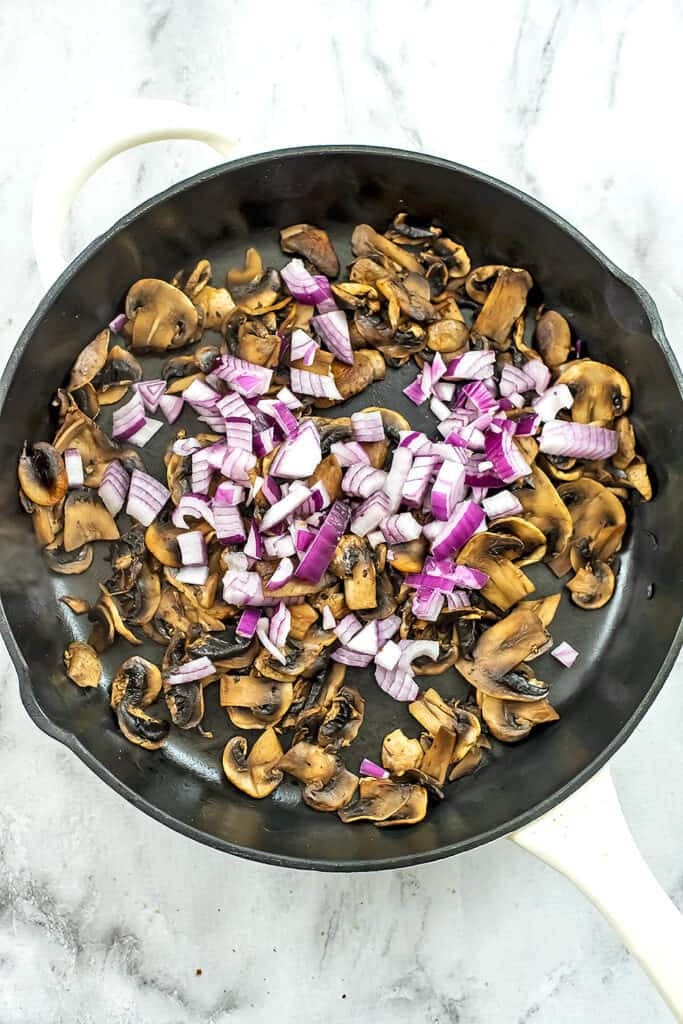 Cooked mushrooms and red onions in a skillet.
