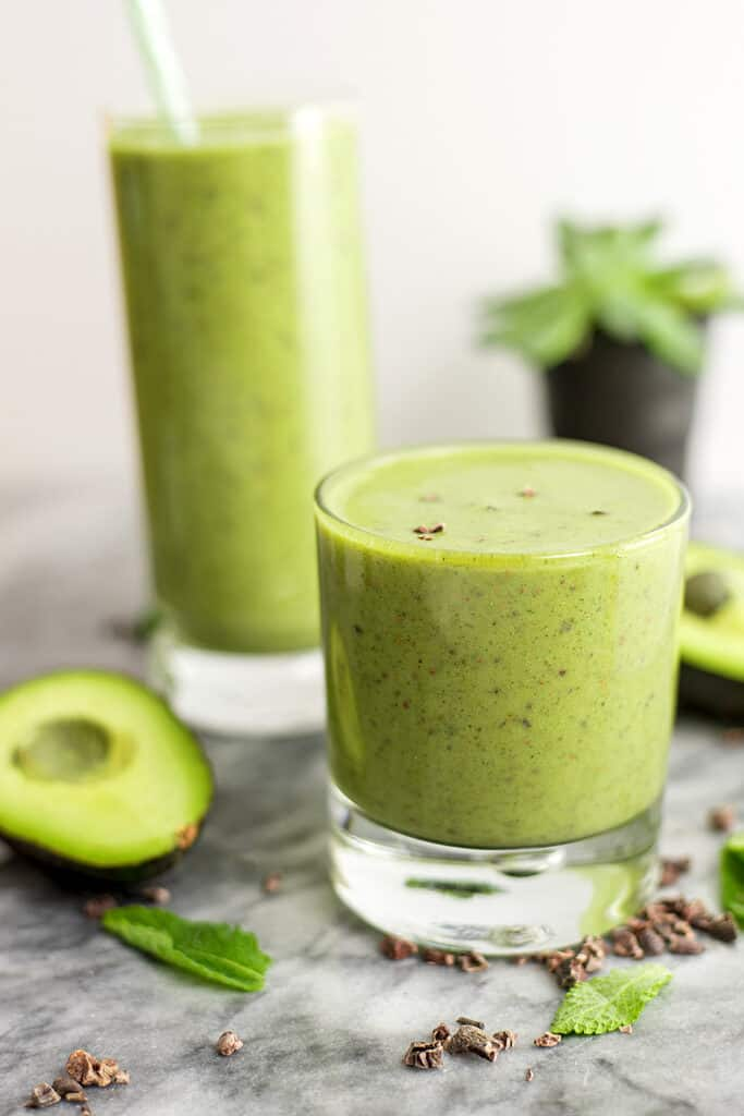 Mint avocado protein shake in a short glass.