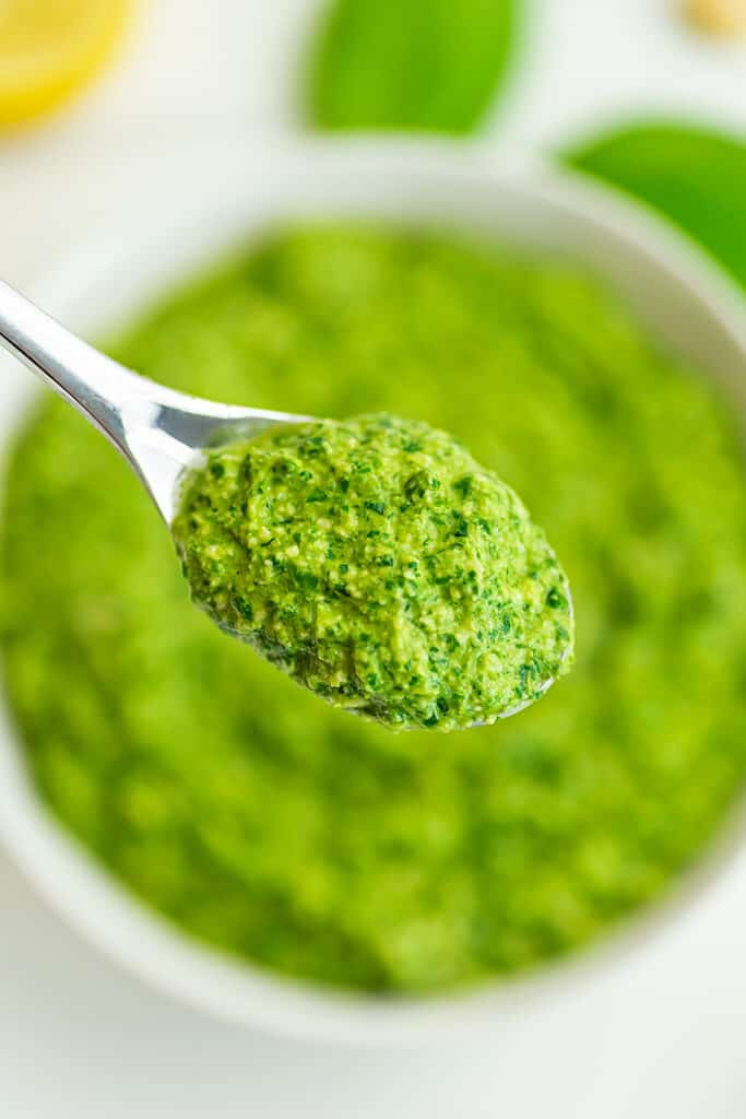 Spoonful of pesto over a bowl.