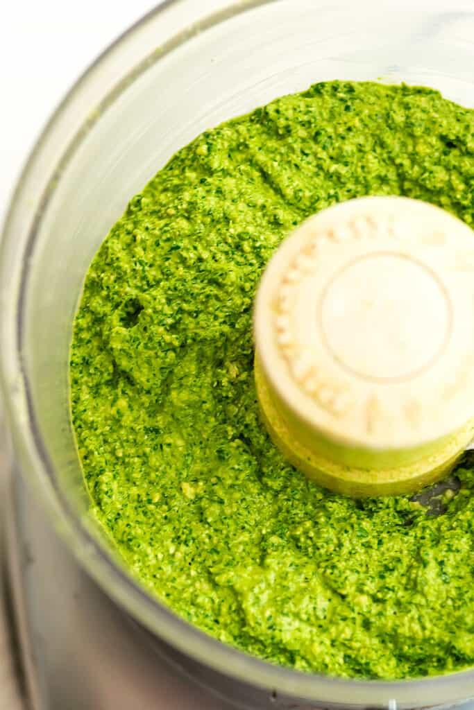 Food processor filled with vegan arugula pesto.