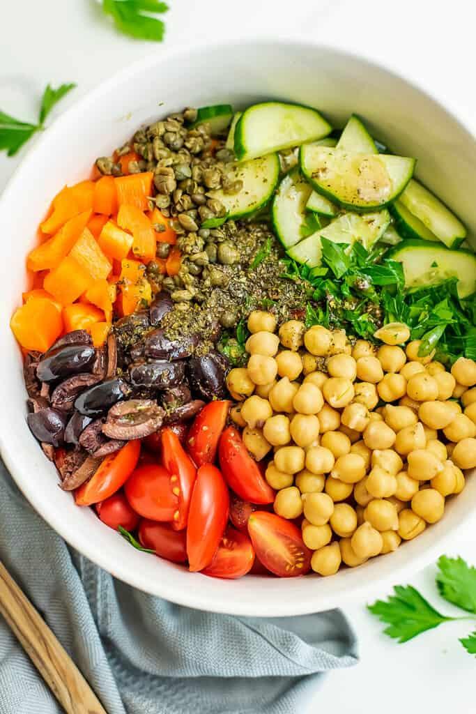 Chopped Mediterranean Salad in a white bowl over blue napkin.