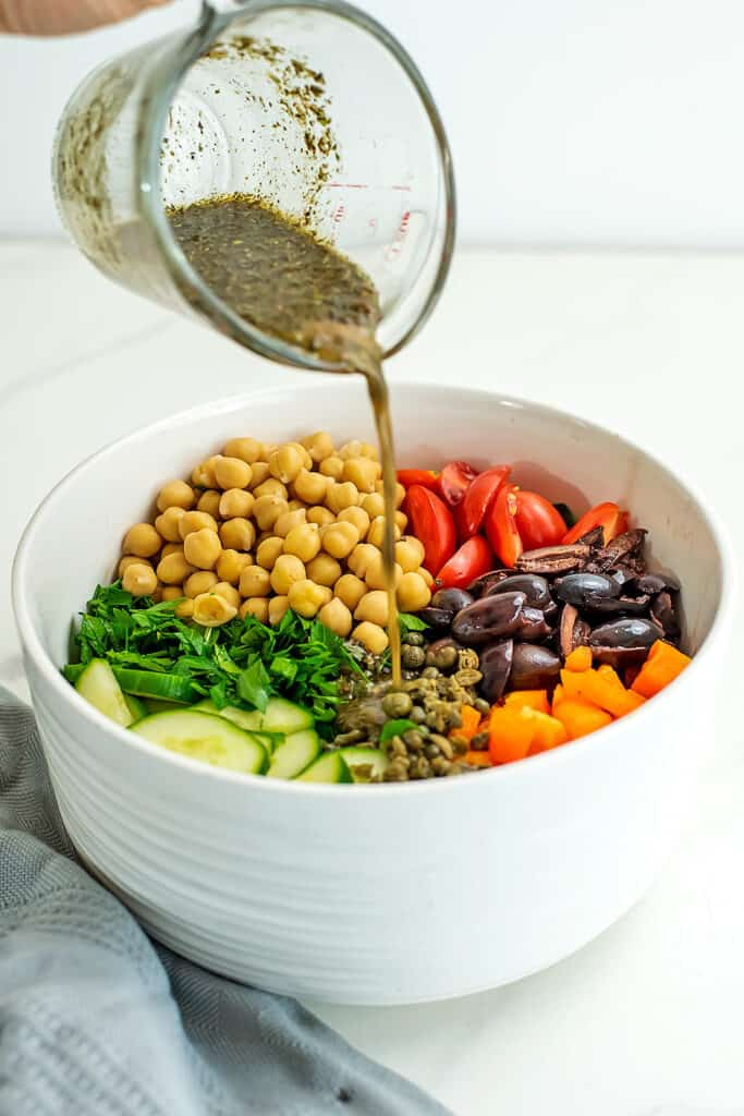 Dressing being poured into a bowl of salad.