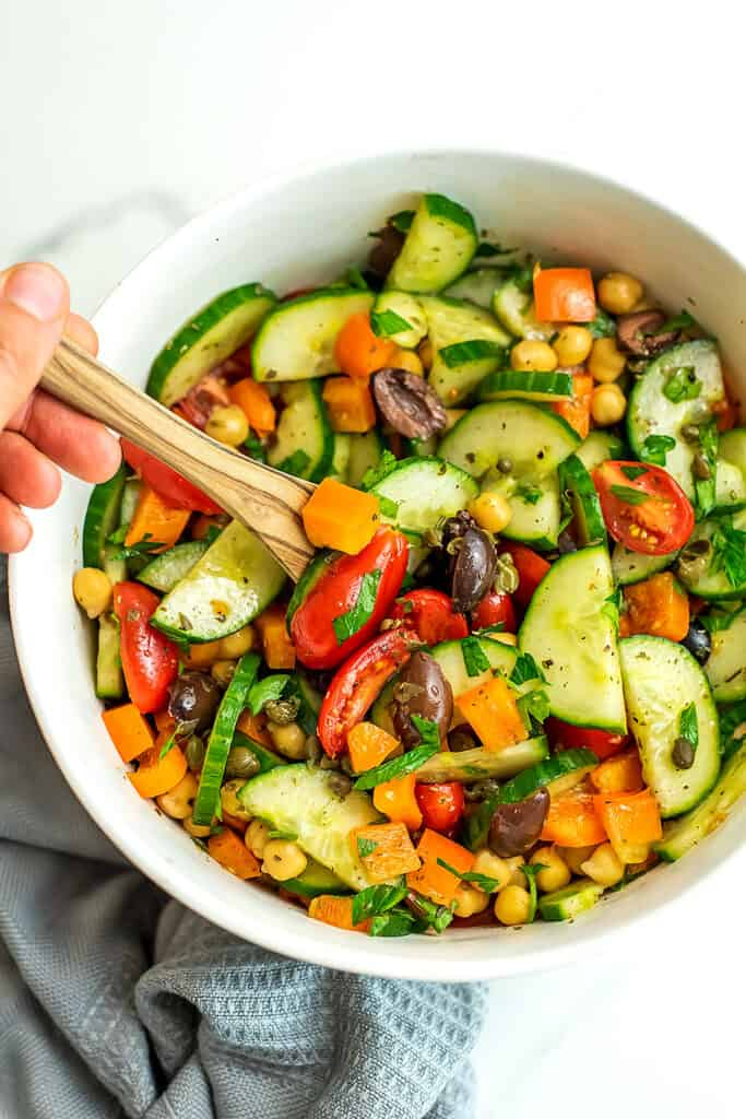 Wooden spoon in a bowl of Mediterranean Chopped Salad.