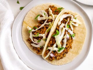 Two cauliflower lentil tacos on a plate.