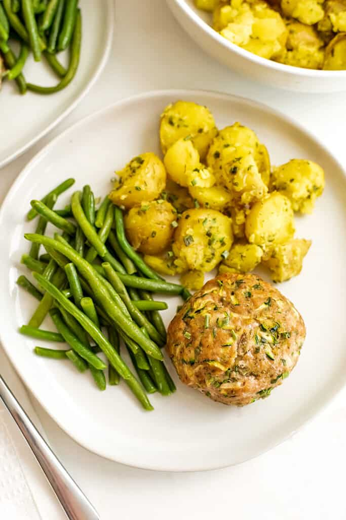 Ranch turkey meatloaf on a plate with green beans and golden potatoes.