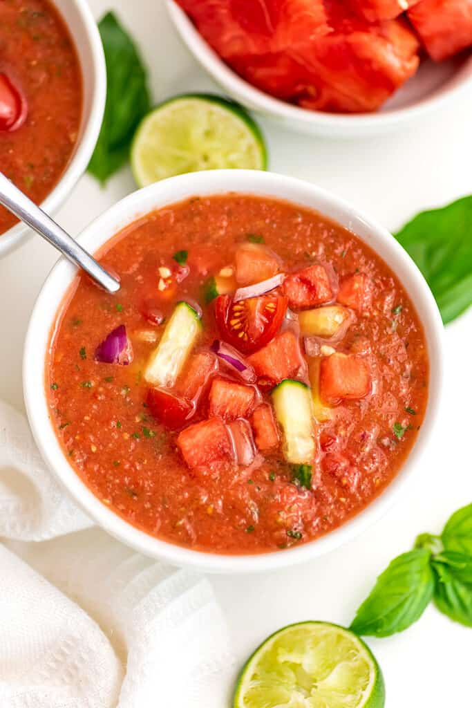 Watermelon gazpacho in white bowl with a spoon in the bowl.