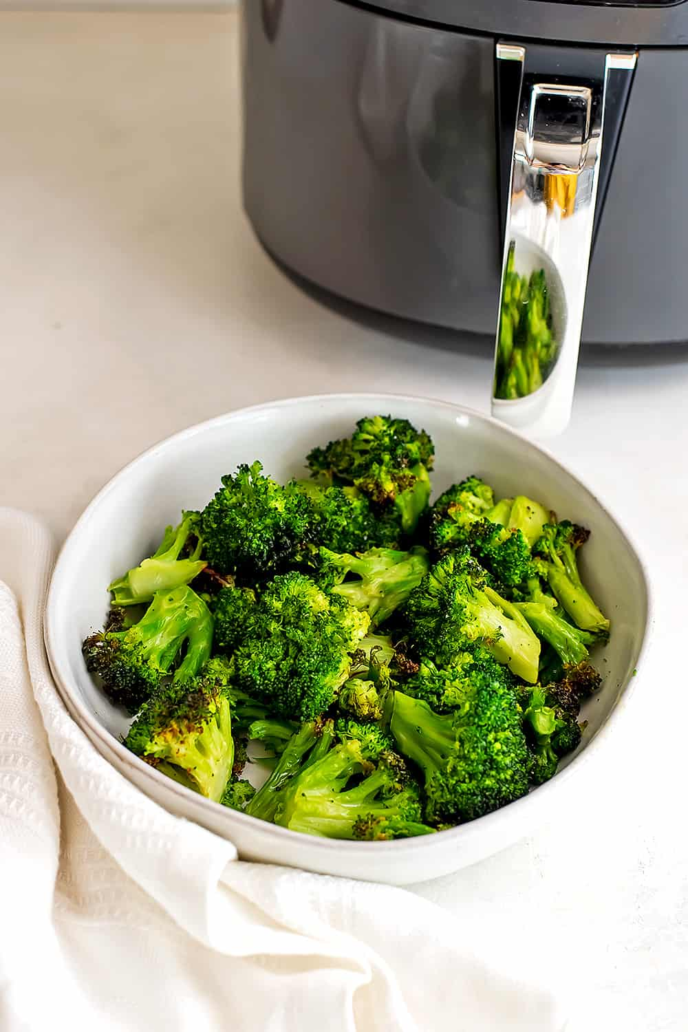 Broccoli in a white bowl in front of the air fryer.