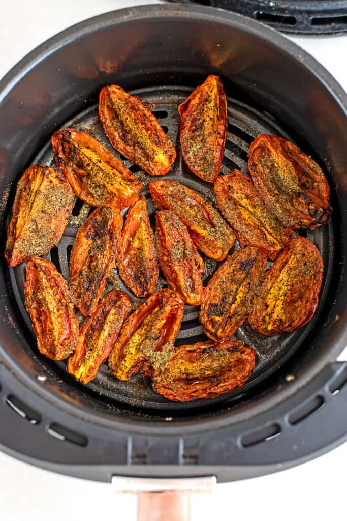 Roma tomatoes in the air fryer basket after roasting.