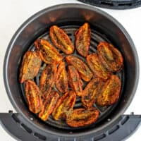 Roasted roma tomatoes in the air fryer basket.