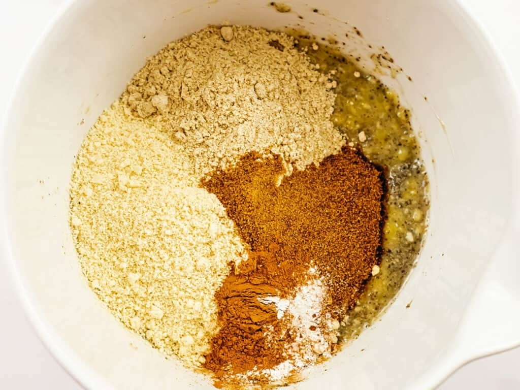 Dry ingredients for almond flour banana muffins in a bowl with mashed bananas.