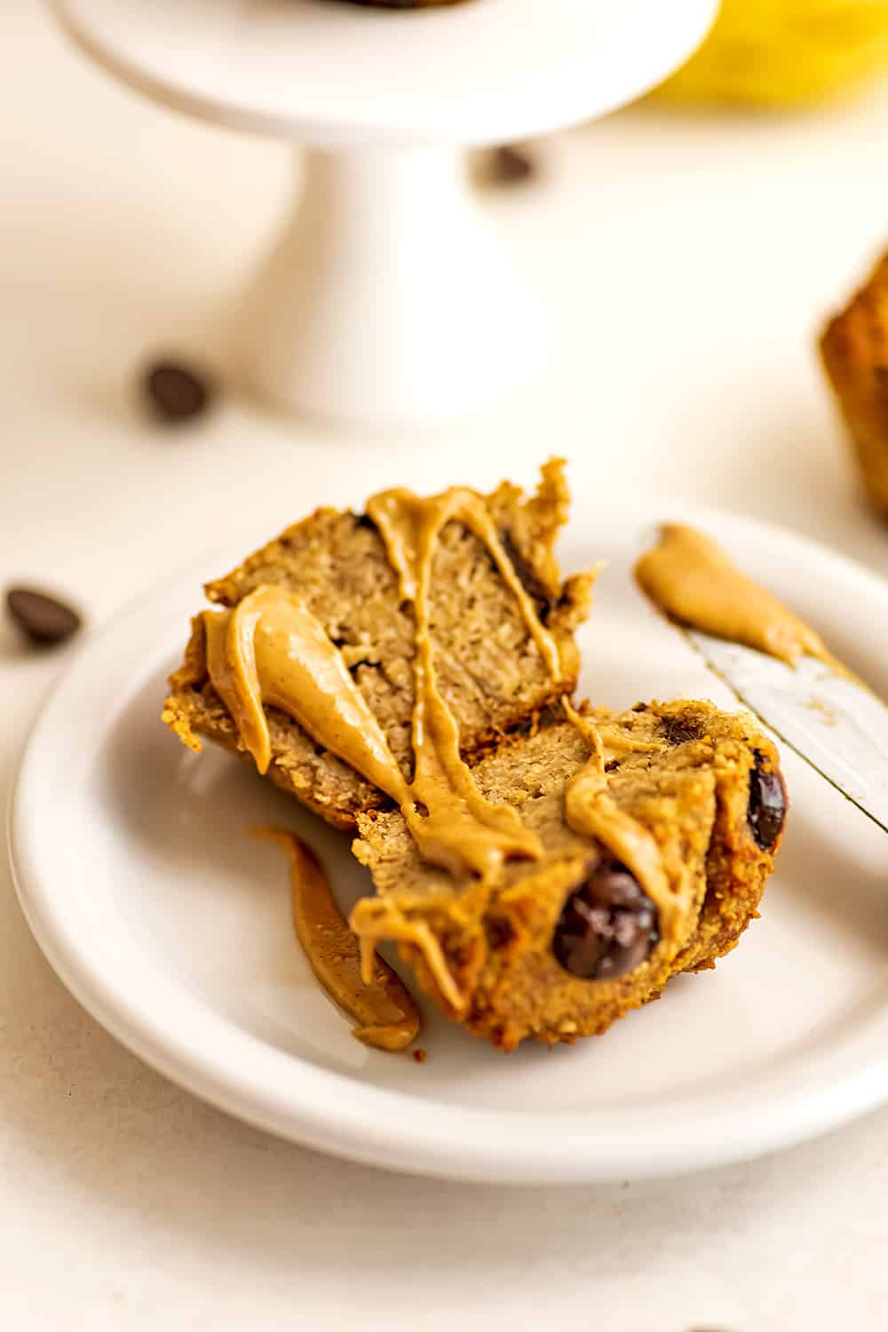Almond flour banana muffin cut in half with peanut butter drizzled.