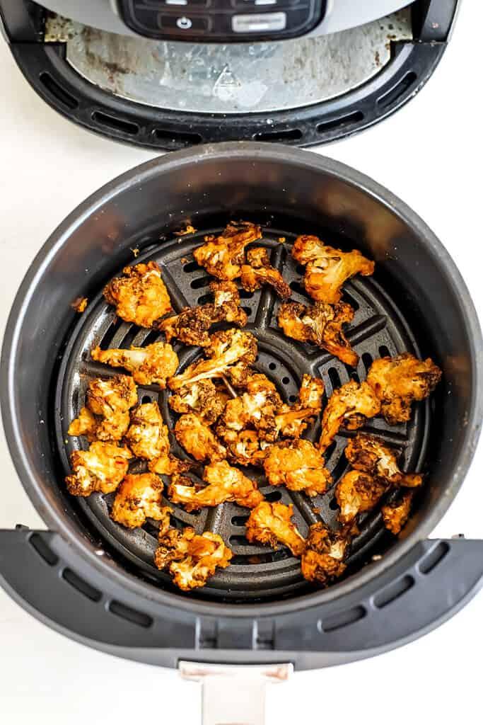Buffalo cauliflower in an air fryer basket after cooking.
