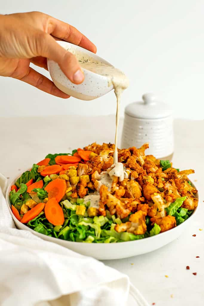 Tahini ranch dressing being poured over buffalo cauliflower salad.