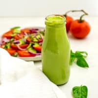 Bottle of creamy basil dressing in front of a plate of tomatoes.