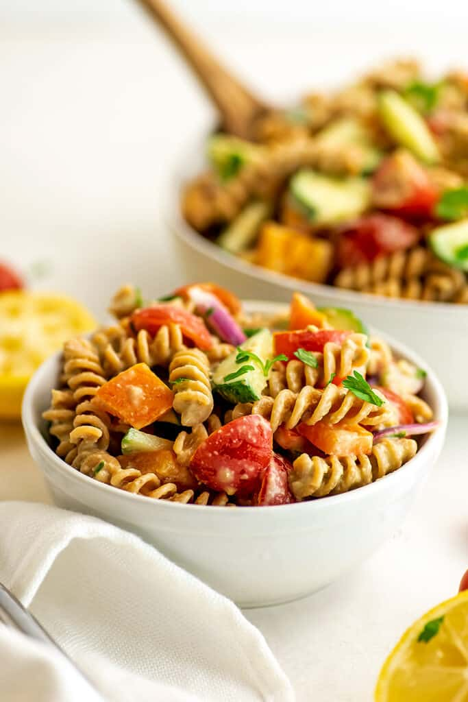 Hummus pasta salad in small white bowl with larger bowl in background.