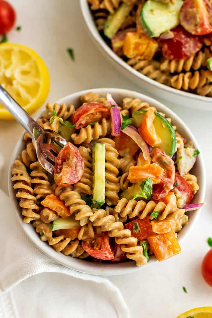 Fork in a bowl of vegan hummus pasta salad.
