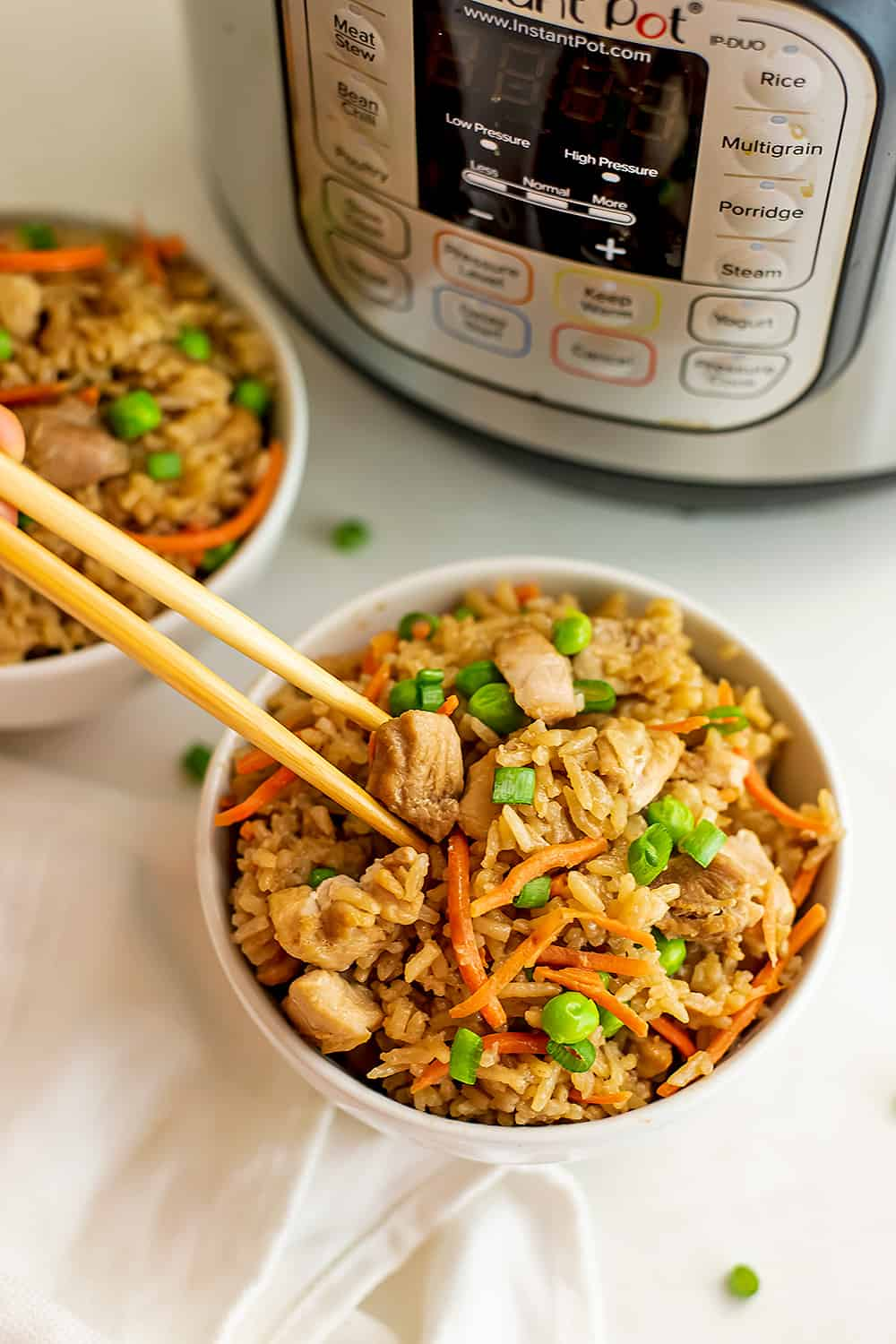 Chopsticks getting a serving of chicken fried rice in front of instant pot.