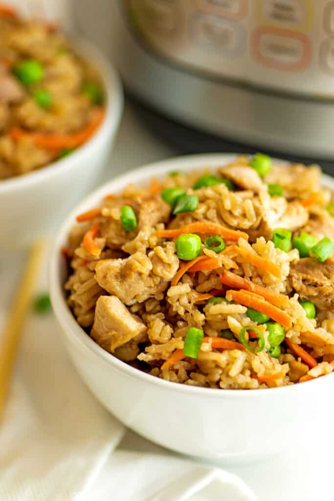 Chicken fried rice in a white bowl in front of instant pot.