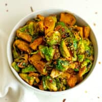 Sriracha brussel sprouts in a white bowl.