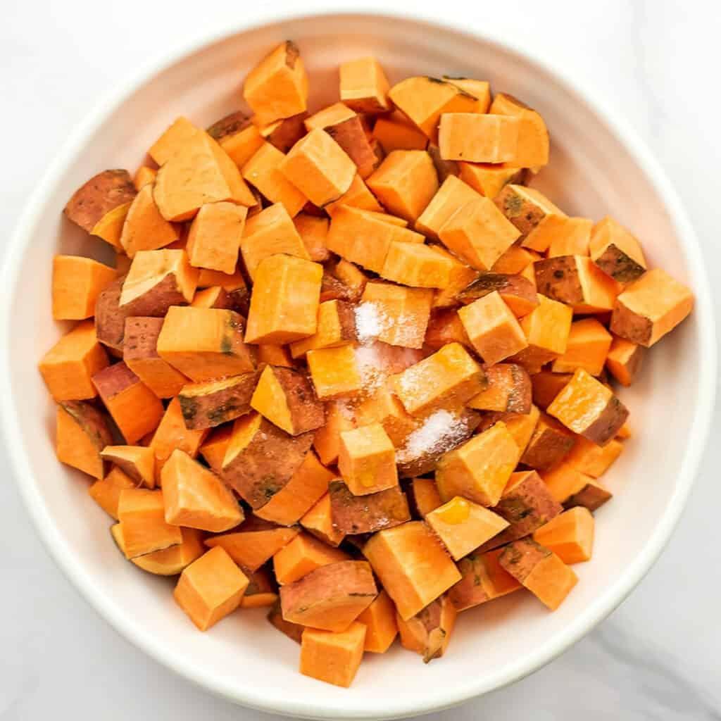 Cubes of sweet potatos in white bowl with seasoning on top.