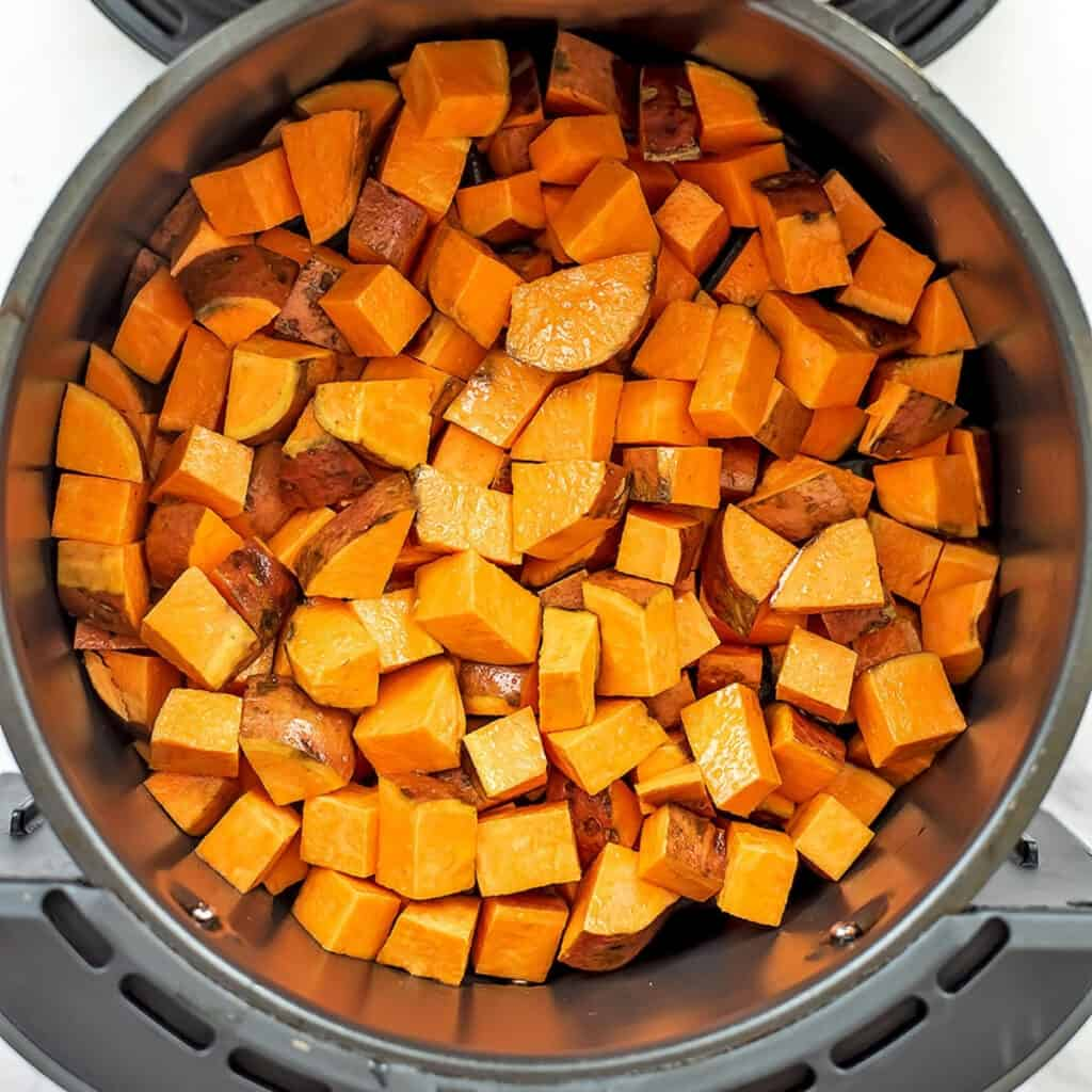 Raw sweet poatoes in air fryer before cooking.
