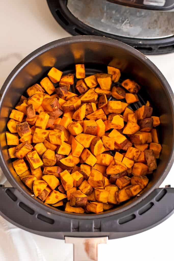 Cooked sweet potato chunks in air fryer basket.