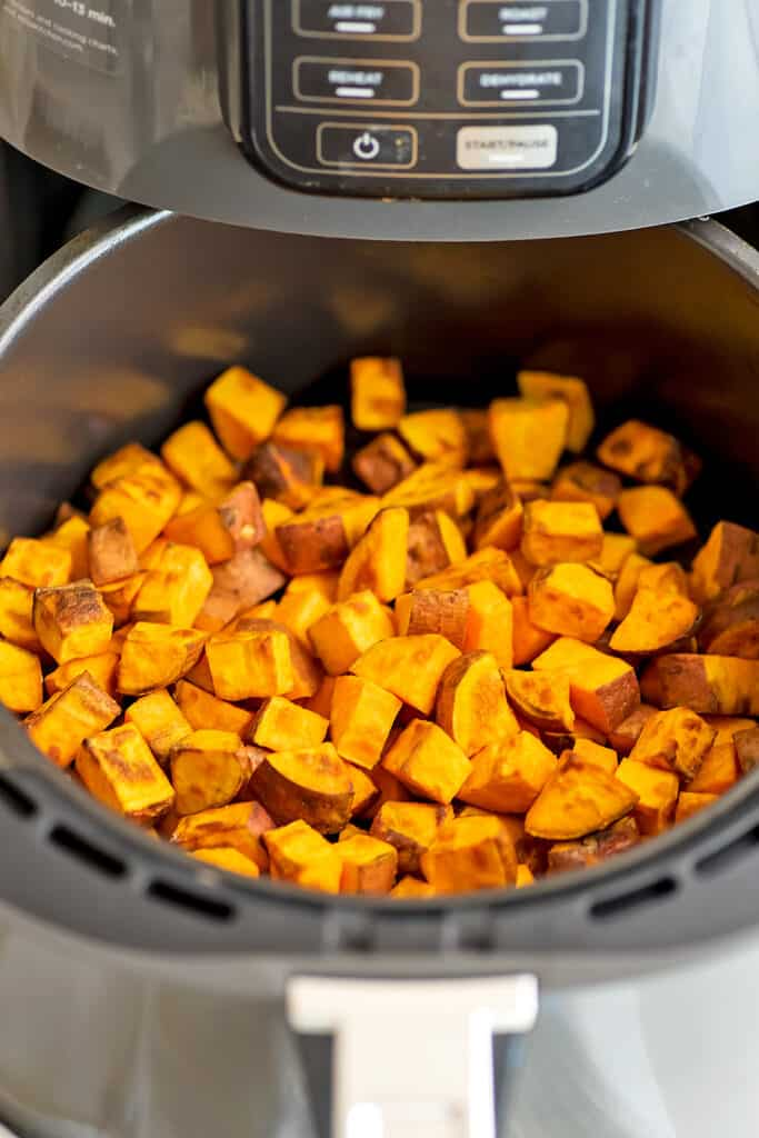 Air fryer filled with sweet potato cubes after cooking.